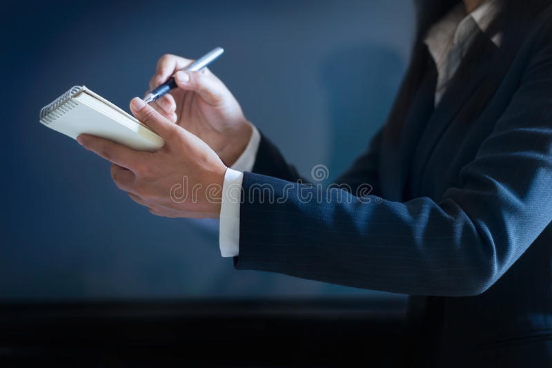 Business woman taking notes in paper on dark blue background royalty free stock images