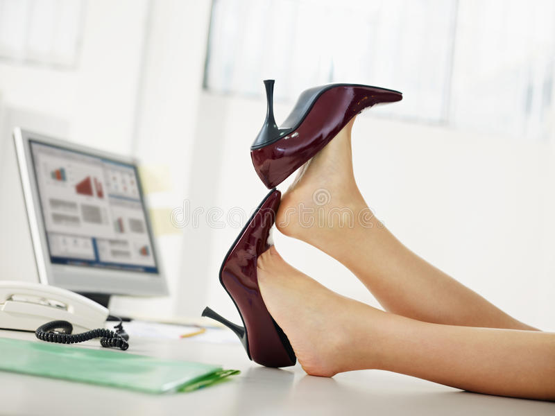 Business woman taking off shoes. In office stock photo