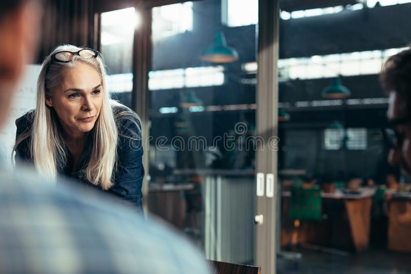 Business woman talking with colleagues in meeting royalty free stock photo
