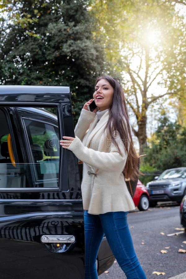 Business woman talking on her mobile phone whilst steps into a black taxi royalty free stock images