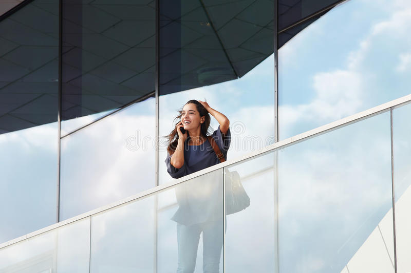 Business woman talking on the mobile phone outdoors. Portrait of business woman talking on the mobile phone with office building in the background royalty free stock image