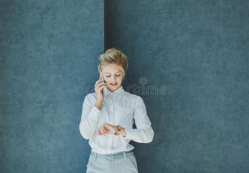 Business woman talking on the phone. Busy business woman talking on the phone and looks at the watch stock photo