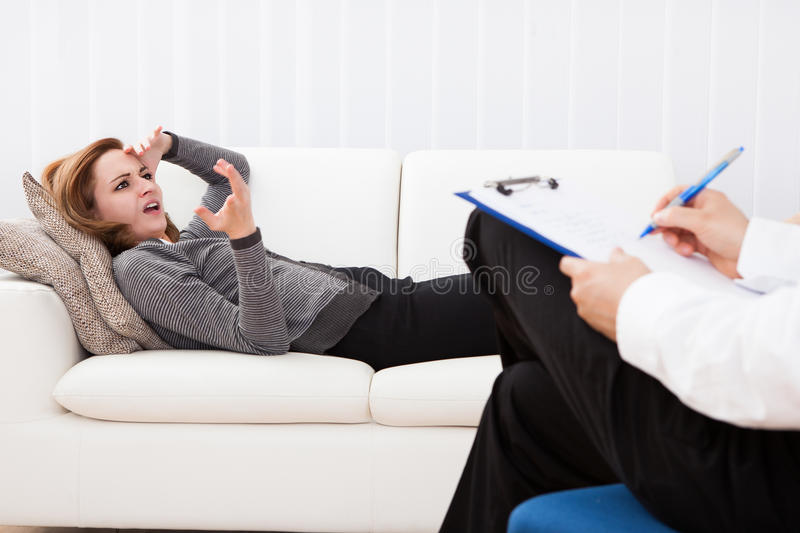Business woman talking to his psychiatrist explaining something. Business women reclining comfortably on a couch talking to his psychiatrist explaining something royalty free stock image