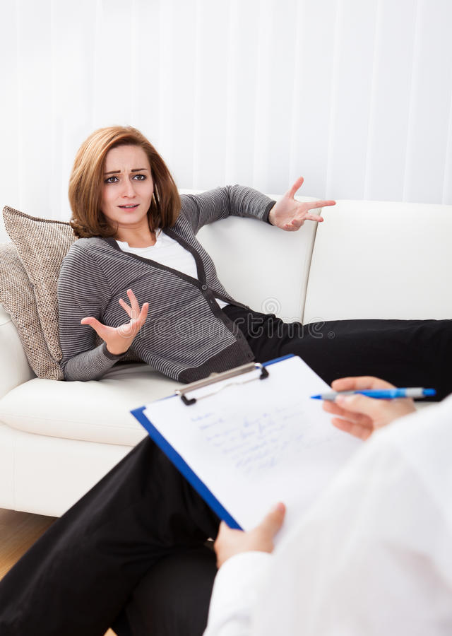 Business woman talking to his psychiatrist explaining something. Business women reclining comfortably on a couch talking to his psychiatrist explaining something stock image