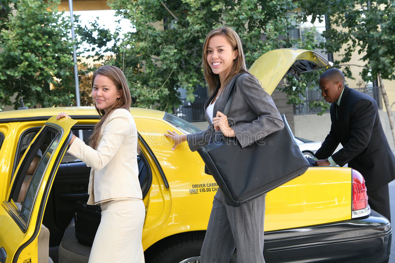 Business Woman in Taxi. A pretty business woman getting into a taxi cab stock image