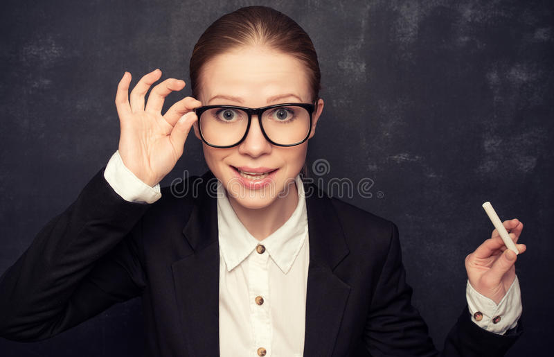 Business woman teacher with glasses and a suit with chalk at a. Business woman teacher with glasses and a suit with chalk the lost in thought at a school board stock image
