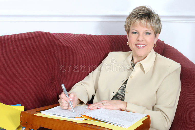 Business Woman or Teacher Working at Home on Couch. Woman in business suit looking up from papers. Shot with the Canon 20D