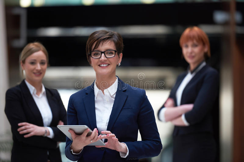 Business woman team. Young business women group, team standing in modern bright office and working on tablet computer royalty free stock photography