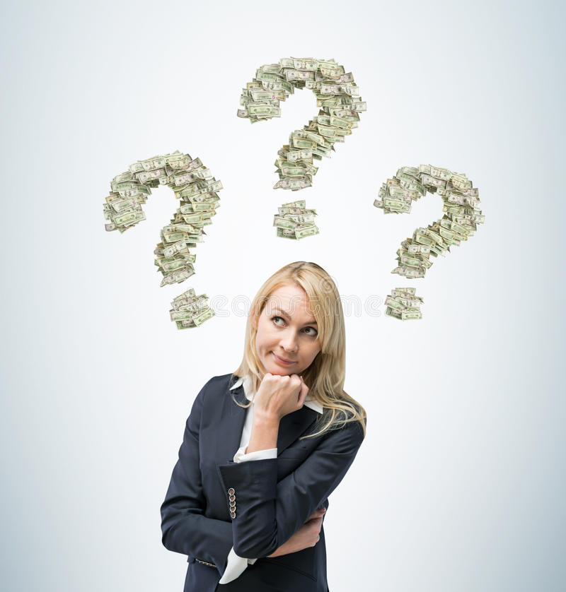 Business woman is thinking about business ideas. Three question signs are made of dollar notes. stock image