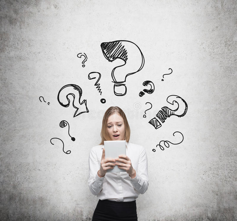 Business woman is thinking about complicated questions. Drawn question marks on the dark wall. stock images