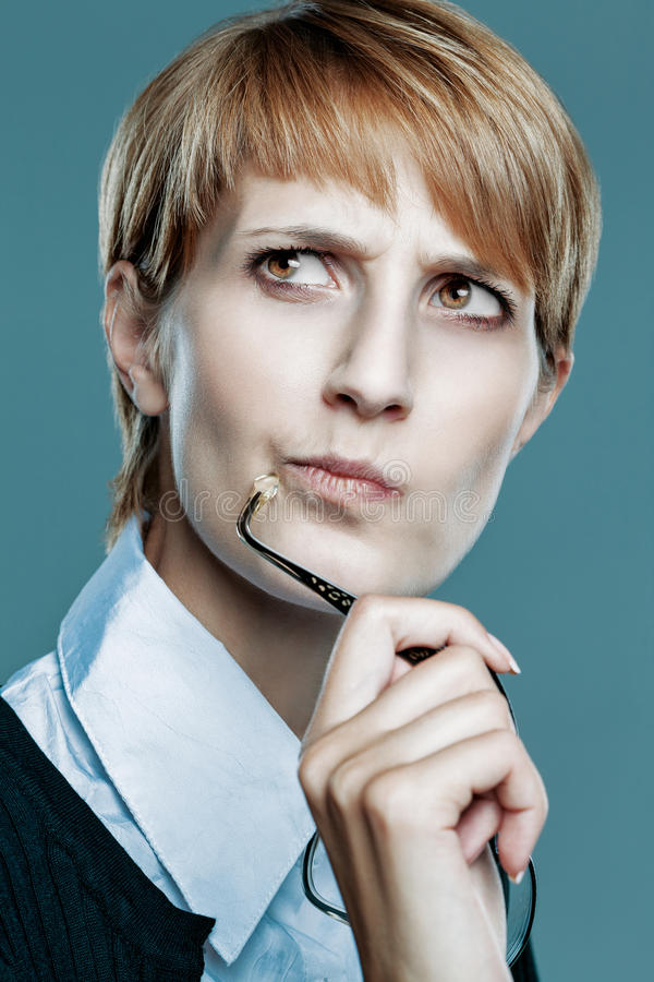 Business woman thinking and holding her glasses royalty free stock image