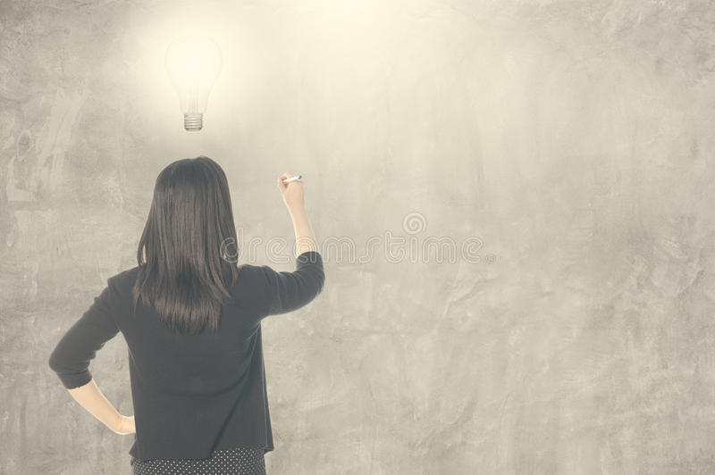 Business woman thinking idea bulb and writing on blank wall for text and background. Business woman thinking idea bulb and writing on blank wall for text royalty free stock images