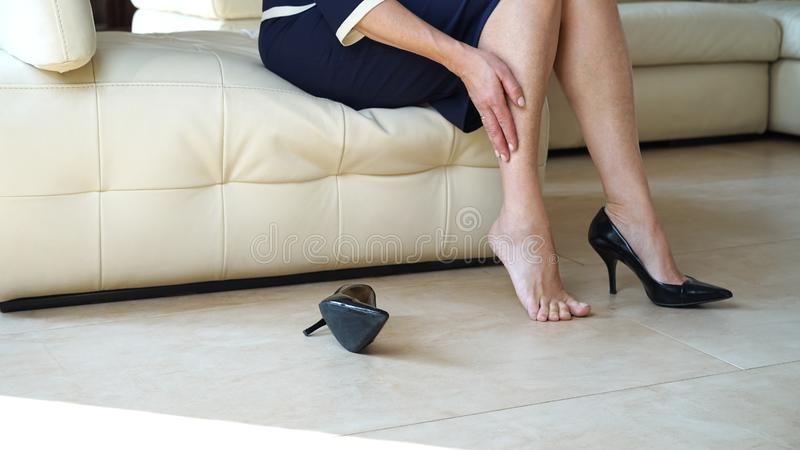 Business woman touching feet with hand. Cropped side view portrait bottom view of woman`s legs and black high heels shoes. Lady. Business woman touching feet royalty free stock photography