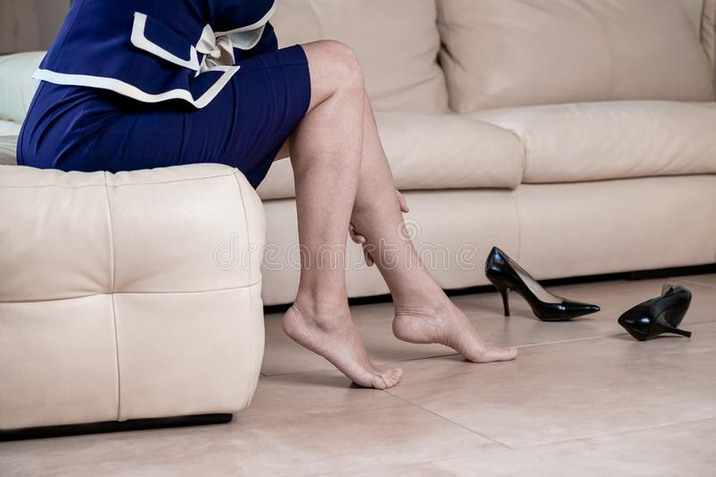 Business woman touching feet with hand. Cropped side view portrait bottom view of woman`s legs and black high heels shoes. Lady royalty free stock images