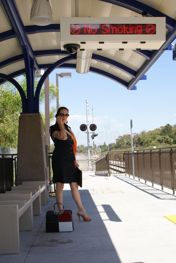Business Woman at Train Station. Beautiful business woman at train station waiting for train talking on cell phone standing under a No Smoking sign stock images