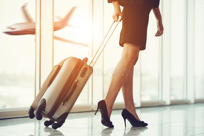 Business Travel. Business people at airport. Airport hall with panoramic windows. Business woman traveling with trolley. Women`s legs, close-up stock photography