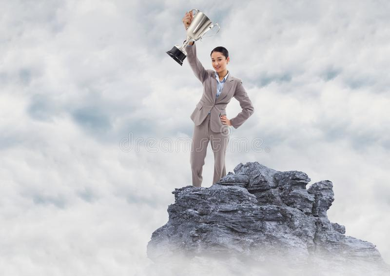 Business woman with trophy on mountain peak in the clouds stock photography