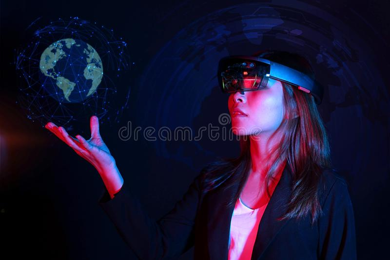 Business woman try vr glasses hololens in the dark room | Portrait of young asian girl experience ar | Future technology concept stock photo