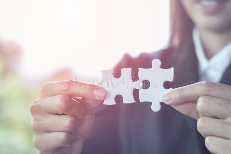Business woman is trying to connect couple puzzle piece. Symbol of association and connection. Concept of business strategy royalty free stock photos