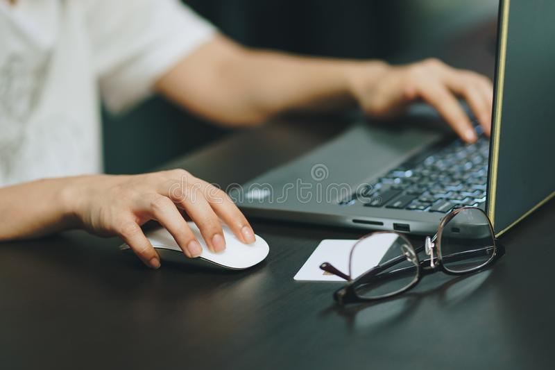 Business woman typing on laptop keyboard and holding computer mouse on black table at coffee shop royalty free stock photos