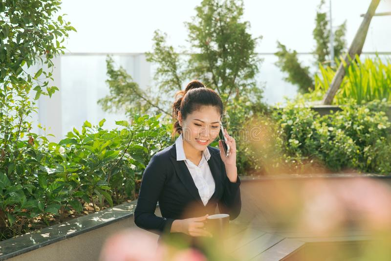 Business woman use smartphone at the garden park stock image