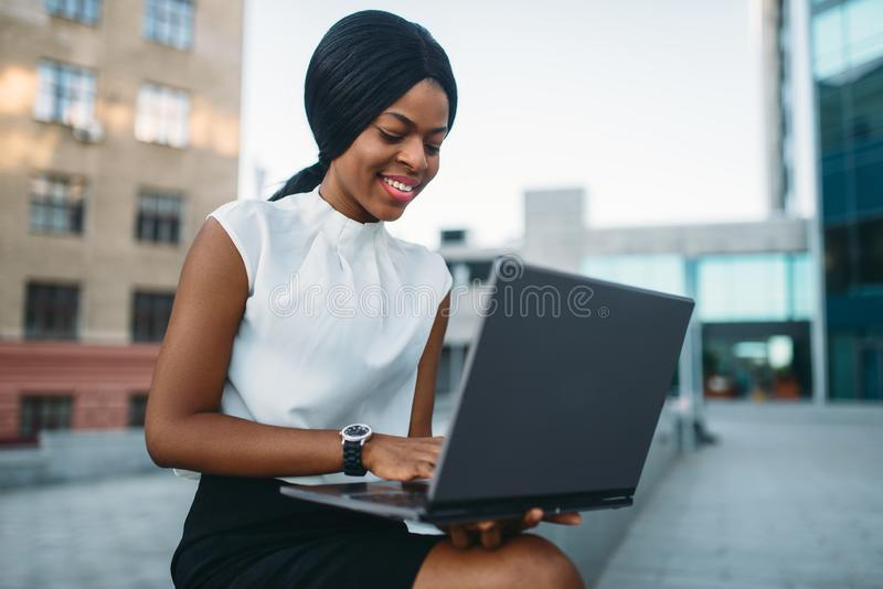 Business woman uses laptop against office building royalty free stock photo