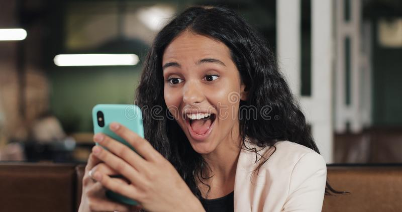 Business woman using app on smartphone sitting in modern office. Beautiful casual female professional in pink suit. Having good news on smartphone royalty free stock photos