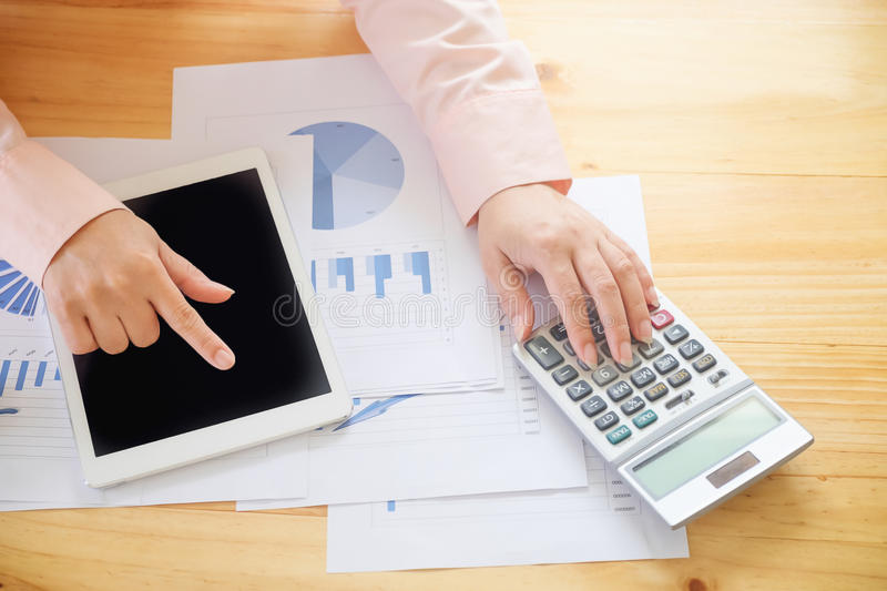 Business woman using a calculator to calculate the numbers stock photos