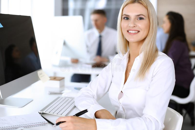 Business woman using computer at workplace in modern office. Secretary or female lawyer smiling and looks happy. Working. Business women using computer at royalty free stock photo