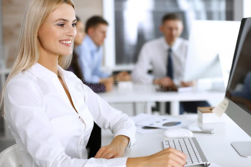 Business woman using computer at workplace in modern office. Secretary or female lawyer smiling and looks happy. Working. Business women using computer at stock photos