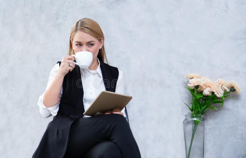 Business woman using digital tablet and drink tea while sitting at cafe, attractive female freelancer holding touch pad. Freelance royalty free stock photography