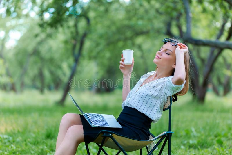Business woman using laptop on lunch break in city park and hold coffe in her hand royalty free stock photo
