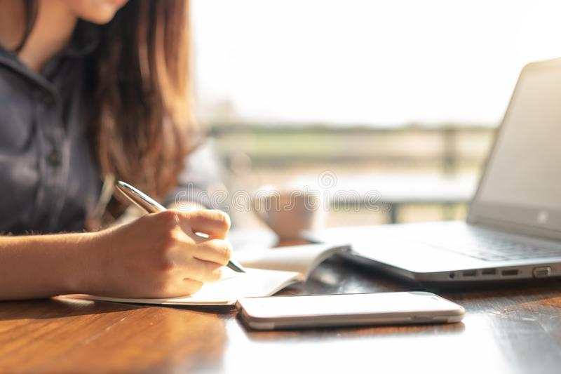 Business woman using laptop and writing on a notepad with a pen at a coffee shop. Working on project concept.  royalty free stock photos