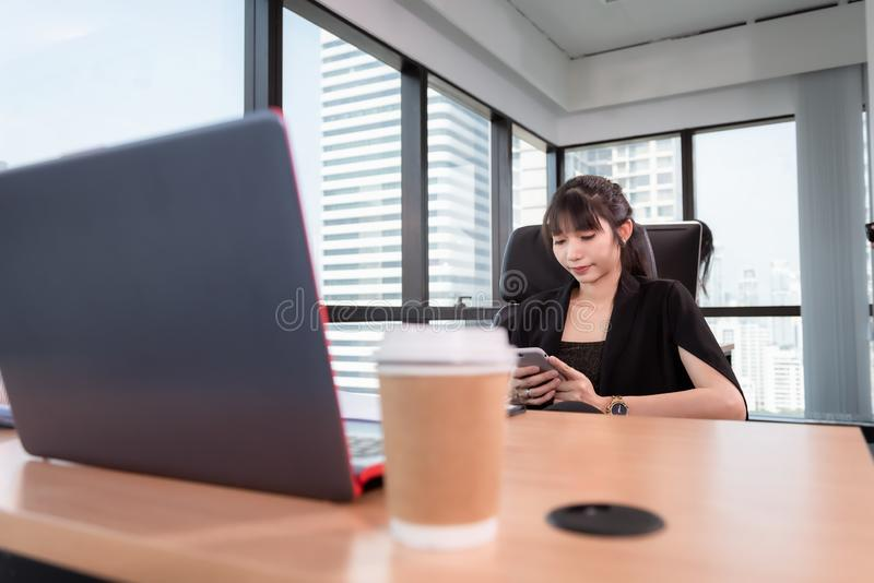 Business Woman Using Mobile Phone While Working in Her Office Desktop, Business Communication and Technology Concept stock photo