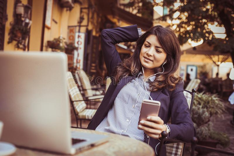 Business woman using smart phone to listening music outside. royalty free stock image