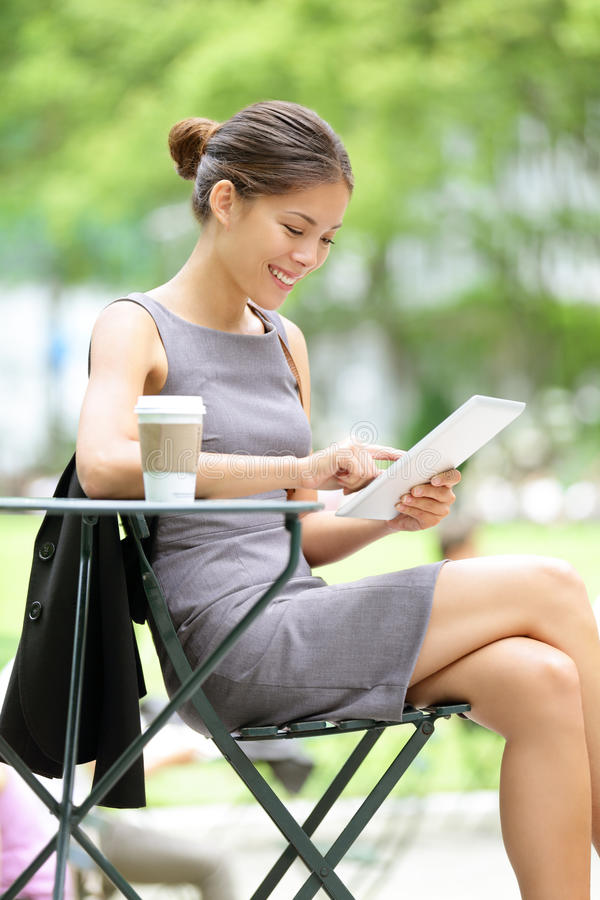 Business woman using tablet on break. Business woman using tablet on lunch break in city park. Young professional businesswoman sitting at table at cafe. Photo royalty free stock images