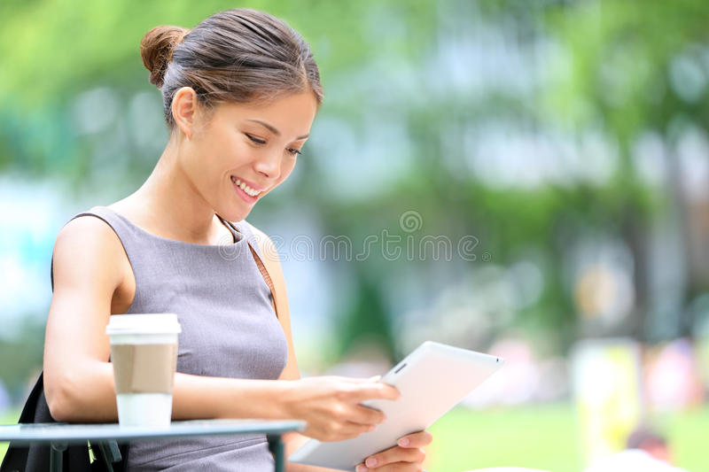 Business woman using tablet on break. Business woman using tablet on lunch break in city park. Young professional businesswoman sitting at table at cafe. Photo royalty free stock photos