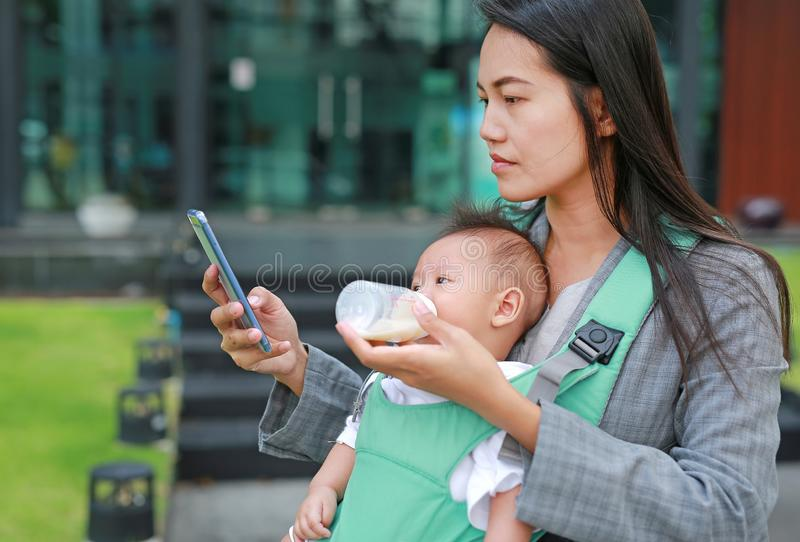 Business woman using telephone with carrying her infant and feeding her child`s by milk bottle. Busy mother hurrying in the royalty free stock photos
