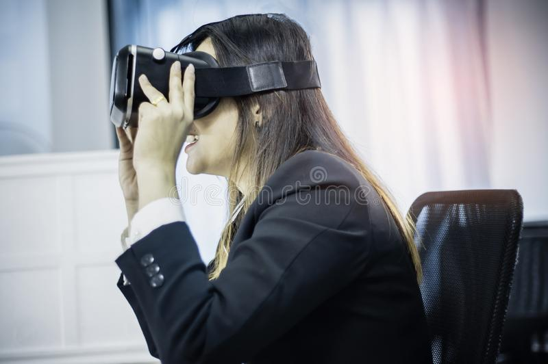 Business Woman using a VR headset for work with virtual reality, with fun and happy new experience, Concept of modern technologies stock photography