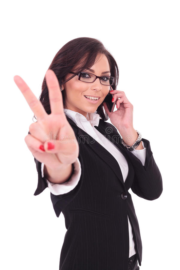 Business woman victory sign & phone. Young business woman showing the victory sign while speaking on the phone and smiling to the camera. on white background stock images