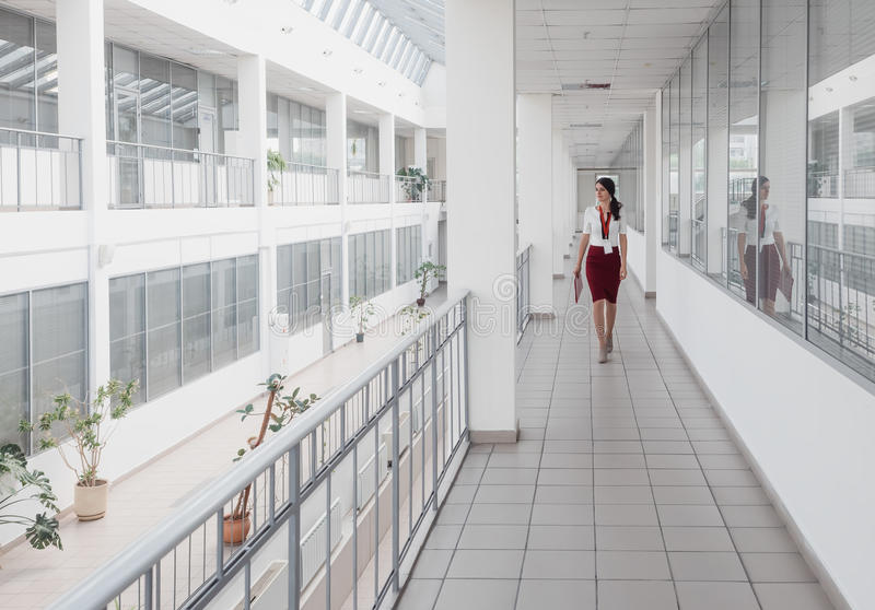 Business Woman Walking Along the Office Corridor. Smiling Businesswoman Goes Against White Offices Background. A young pretty girl royalty free stock photos