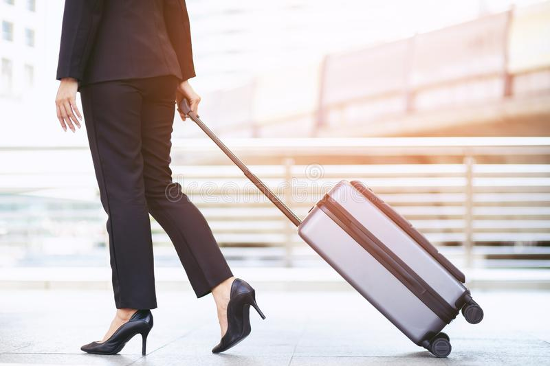 Business woman walking outside public transport building with luggage in rush hour. Business traveler pulling suitcase in modern a royalty free stock photos