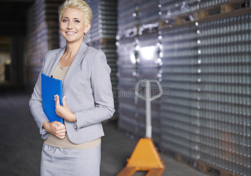 Business woman in warehouse. Professional business woman at warehouse stock photography