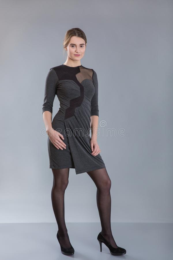 Business woman wearing gray dress staying full-length. Over grey background. model tests stock photo