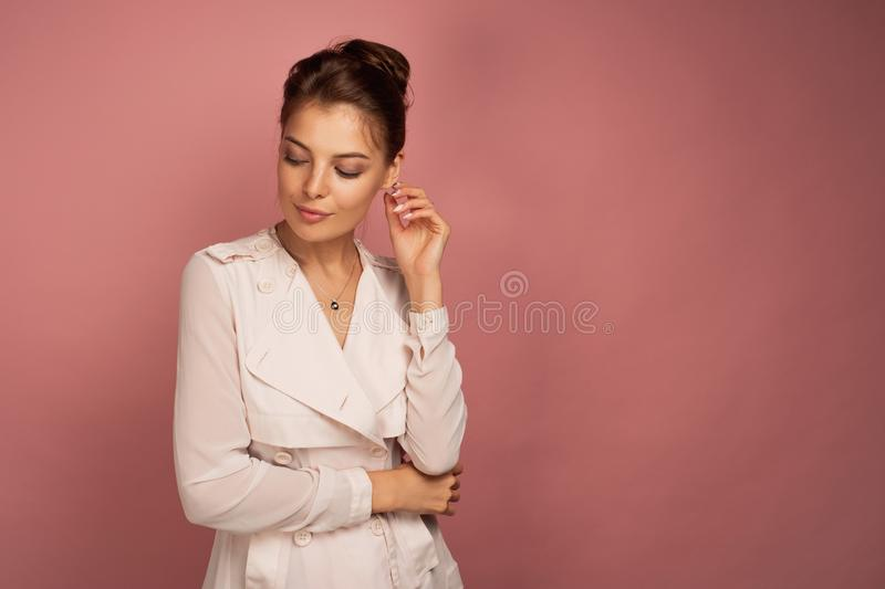 Business woman looks down thoughtfully touching her ear, pink background. Business woman in a white coat looks down thoughtfully touching her ear and posing over stock images
