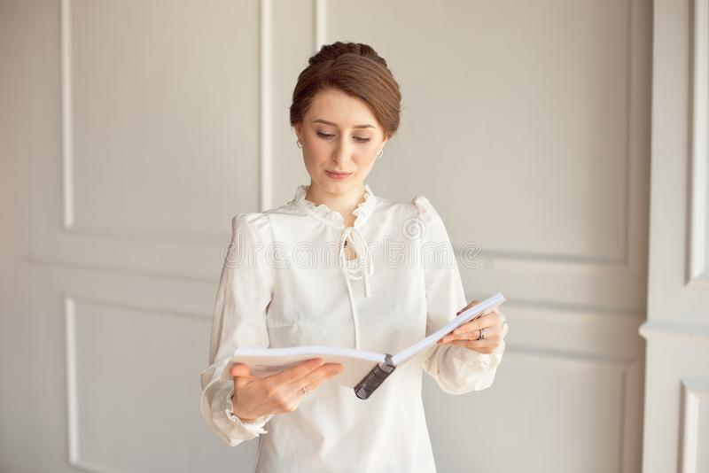 Business woman in a white shirt and black trousers looks documents in hands.  royalty free stock photos