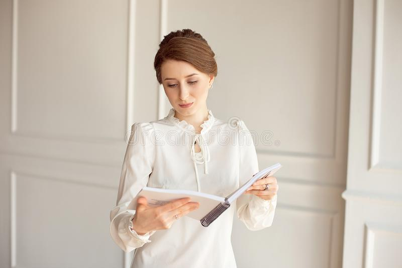 Business woman in a white shirt and black trousers looks documents in hands.  stock images