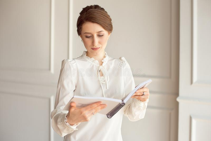 Business woman in a white shirt and black trousers looks documents in hands.  royalty free stock photo