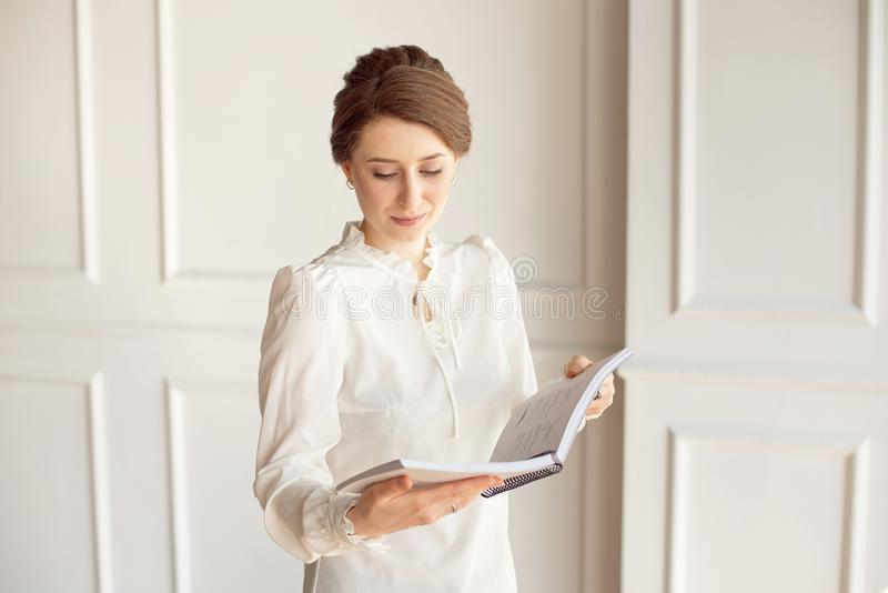 Business woman in a white shirt and black trousers looks documents in hands.  stock photography