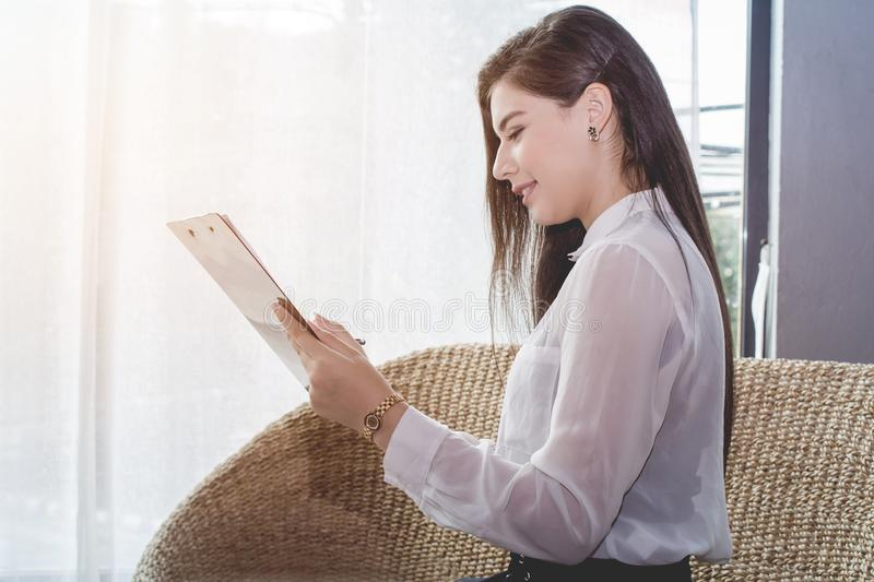 Business woman in white uniform reading report the commercial processes involved in promoting and selling and distributing a produ royalty free stock photo
